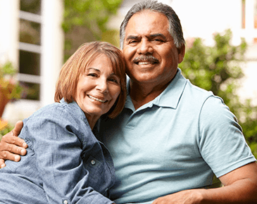 Smiling Couple sitting outside their house | Featured image for CareCredit at Avalon Dental Care, Cosmetic, Restorative, and Implant Dentist in El Segundo and Carson
