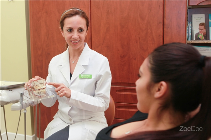 A Doctor Consulting Patient Using Fake Jaw Avalon Dental El Segundo Ca