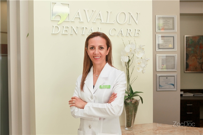 Dr. Kelishadi in front of the Avalon Dental Care Logo | Avalon Dental, El Segundo CA Location