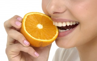 Woman biting into orange