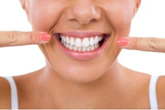 Lady pointing to her straight teeth after her braces were removed | Avalon Dental, your Carson and El Segundo Dentist