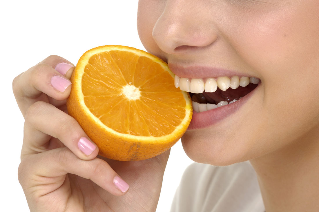Woman taking a bite of a orange | Avalon Dental, your Carson and El Segundo Dentist
