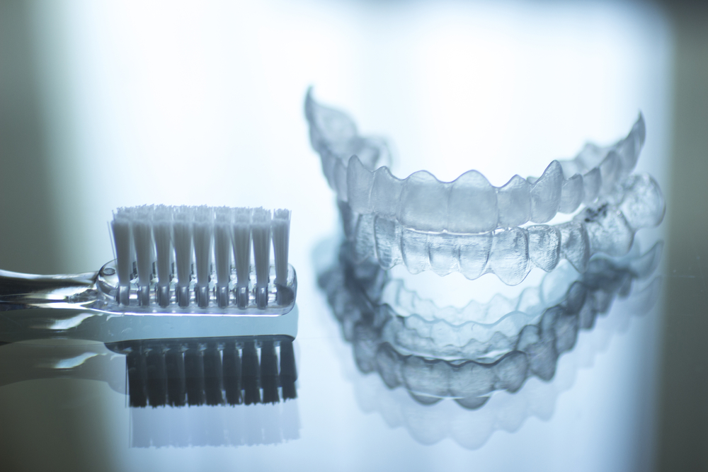 Image of Invisalign clear aligners and a Tooth Brush on a Table | Avalon Dental, your Carson and El Segundo Dentist